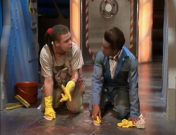 Lister and the Cat from Red Dwarf scrubbing the floor